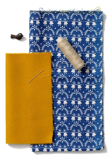 Gult kläde, blått mönstrat bomullstyg, en trådrulle, en nål och en knapp.