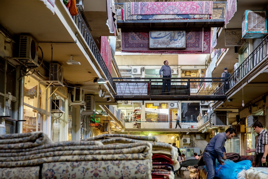 Interiör från en mattbazar med mattor i högar på golvet och hängande i taket.