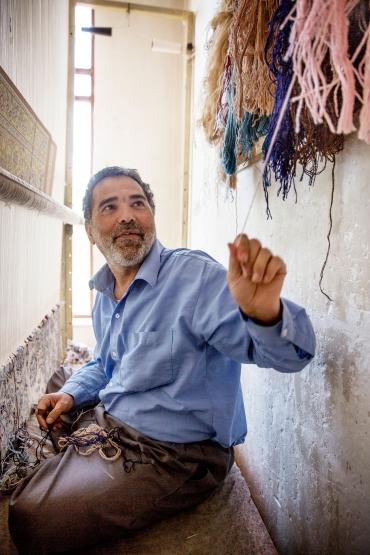 Mazaher Sharifi sitter vid vävstolen.