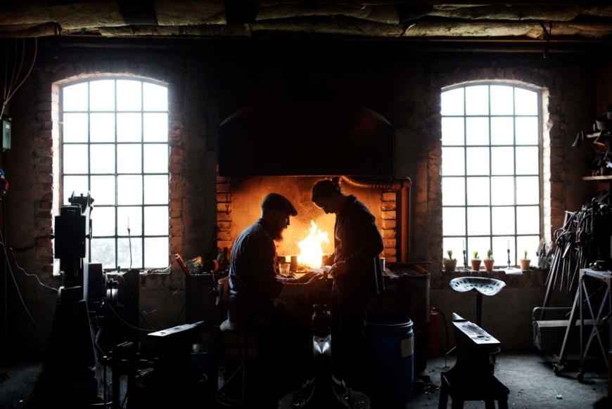 Kristofer Åberg och Julia Kalthoff fram för härden i smedjan. Ljuset faller in genom två stora fönster i bakgrunden.