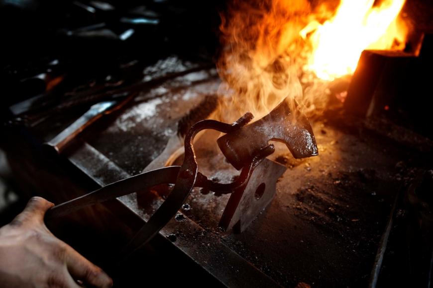 Ett yxhuvud hålls upp med en tång med elden i härden i bakgrunden.