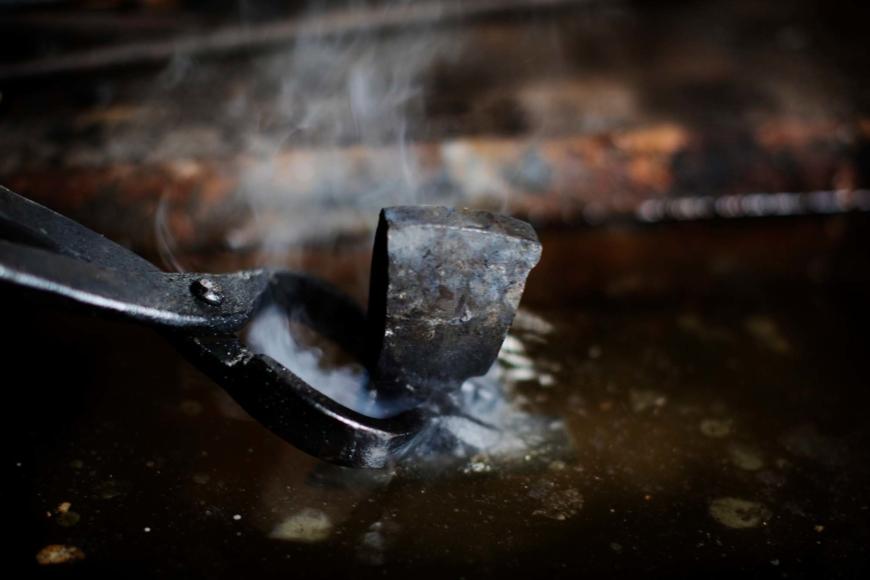 Ett yxhuvud sänks ner i vätska med hjälp av en tång.