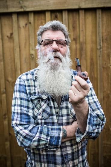 Porträtt av Lars Jönsson rökandes pipa.