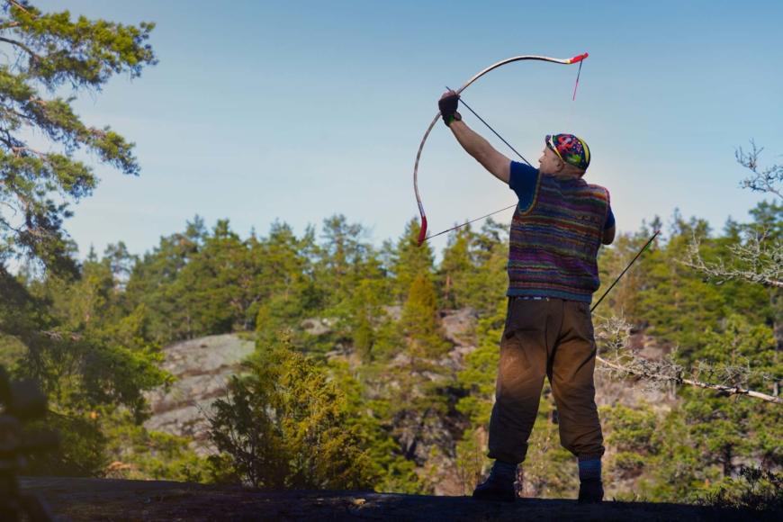 Anders Jakobsen står i skogen och spänner pilbågen.