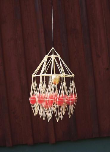 Halmkrona med ett guldfärgat ägg mitt i och romber med röda ulltussar underst.