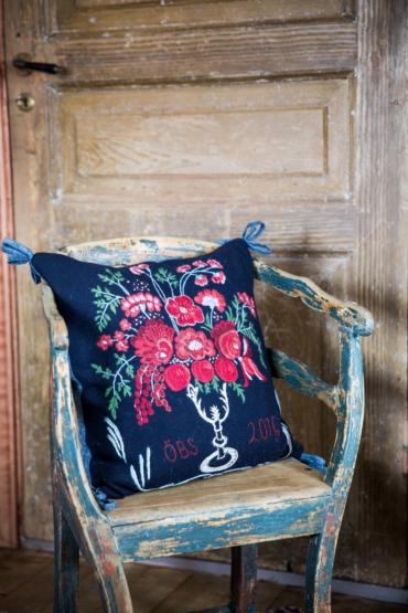 Blå kudde broderad med blommönster i röda och grönatoner placerad i en gammal sliten blå trästol.