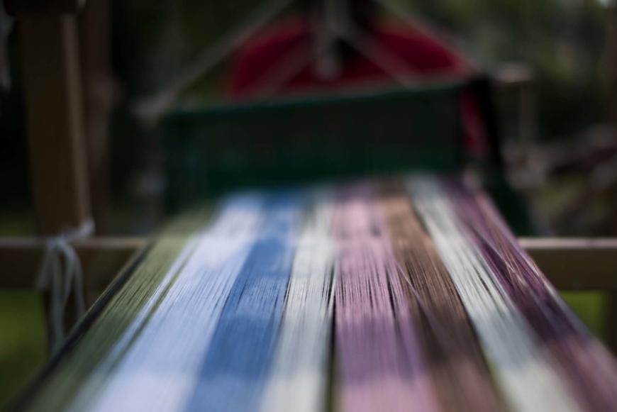 Varp i grönt, vitt,blått, rosa , brunt och lilla går in i vävstolen.