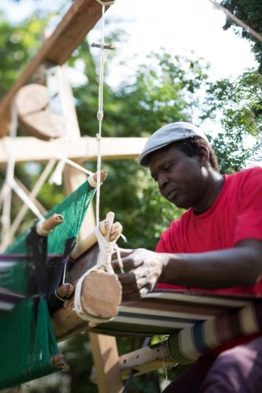 Ousman Sarr sitter och väver vid sin vävstol i en park.