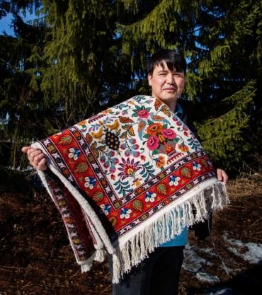 Morteza Golestani håller upp en matta knuten i ullgarn.