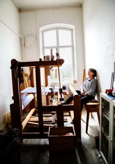 Monica Hallén sitter i sin ateljé. En vävstol tar upp nästan hela rummet.