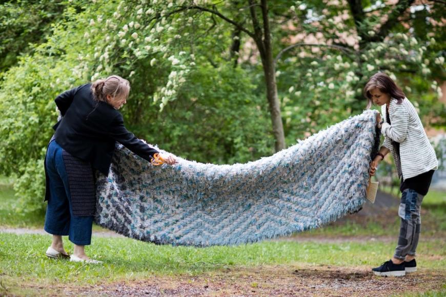 Katarina Evans och Katarina Brieditis med en matta ute på en gräsmatta.
