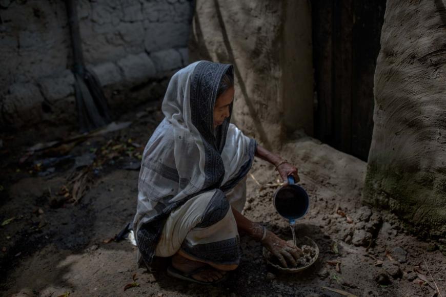Siras Khatun häller vatten över lera i en skål.