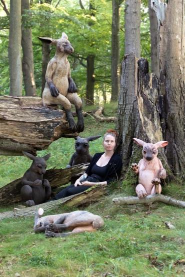 margit Brundin sitter lutad mot ett träd omgiven av sina harar.