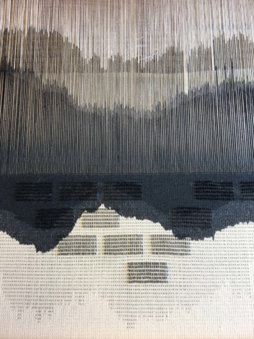 Närbild på sammetstyg i vävstol. Mönster i svart och vitt.