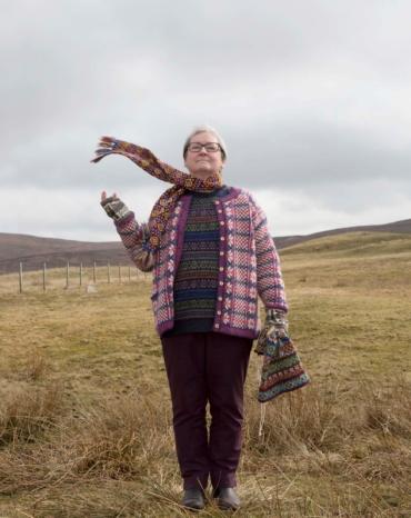 Hazel Tindall stående på heden iklädd Fair isle-stickade tröja, kofta, mössa, halsduk och halvvantar.