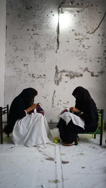 Två kvinnor sitter och syr fotbollar för hand.