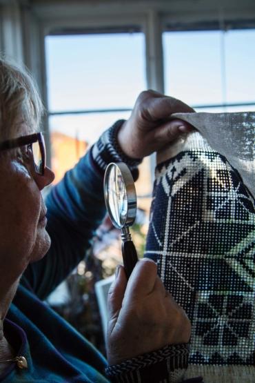 Rose Ericsson granskar en gästrikenäversöm med förstoringsglas.