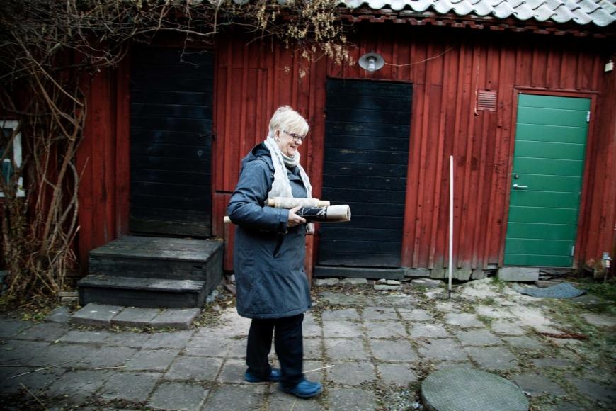 Rose Ericsson på sin innergård med två hoprullade näversömsarbeten.
