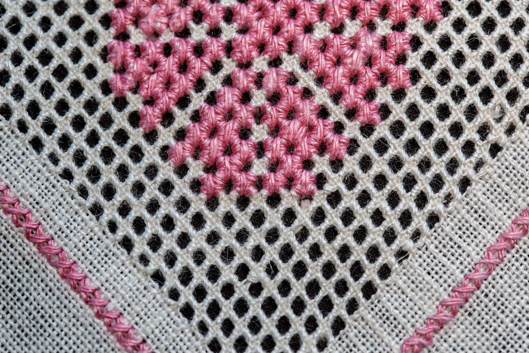 Gästrikenäversöm med rosa mönsterstygn på vit botten.