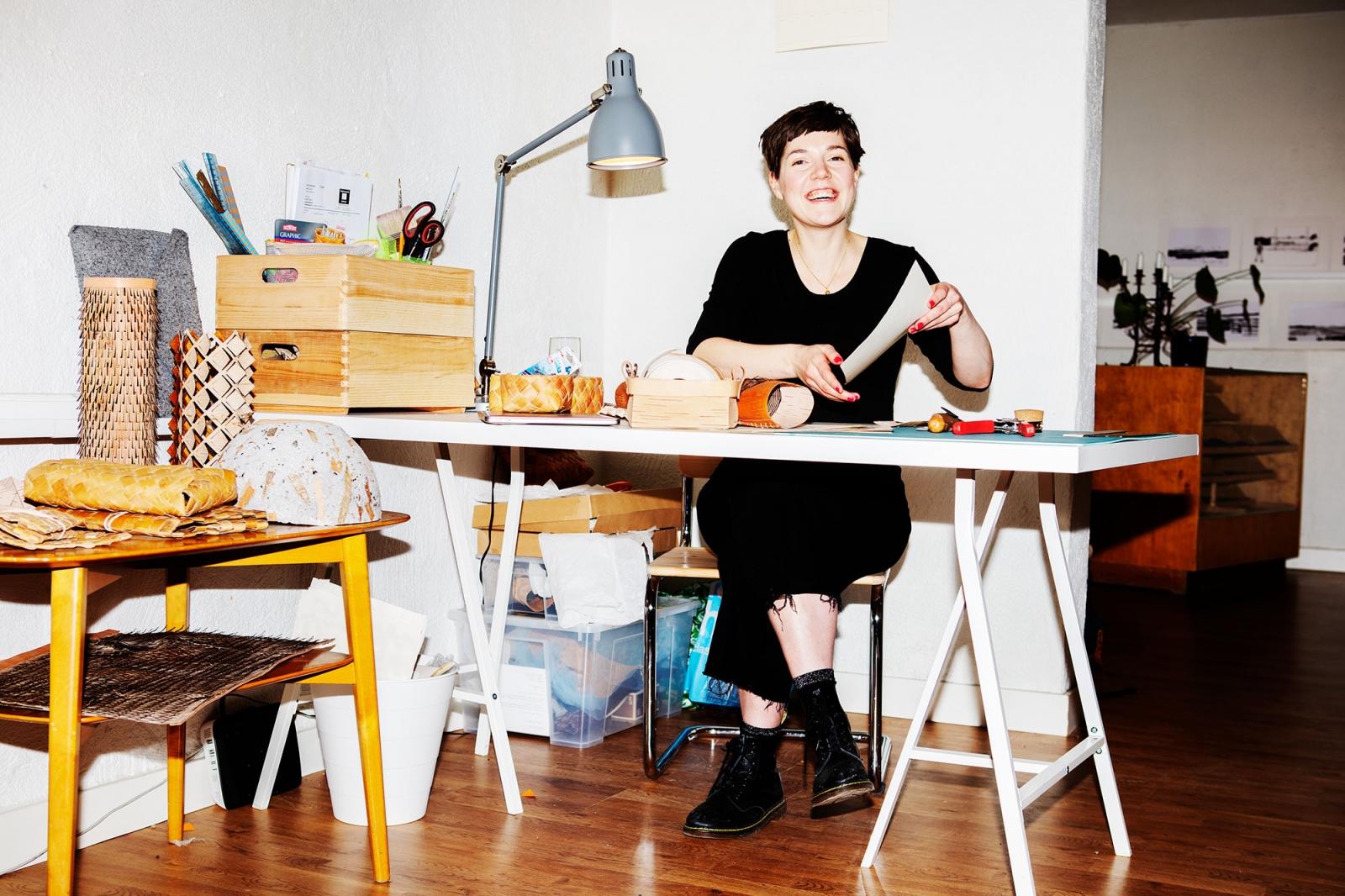 Emma Dahlqvist sitter vid sitt skrivbord och skrattar.