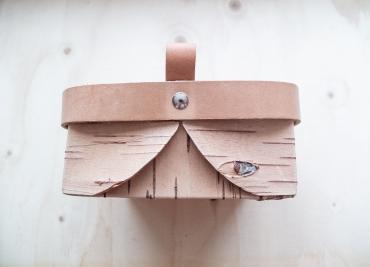 Färdig vikt näverkorg med en nit som håller läderbandet på plats.