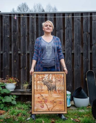 Lina Eriksson står i sin trädgård med en nävertavla som föreställer en älg.