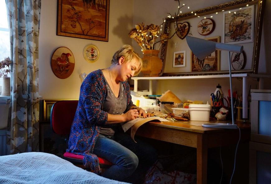 Lina Eriksson sitter vid sitt skrivbord och skär ut små näverbitar.