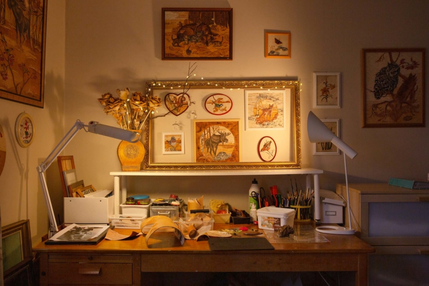 Lina Eriksssons skrivbord med med flera nävertavlor på vägen och näverflak och verktyg på bordet.