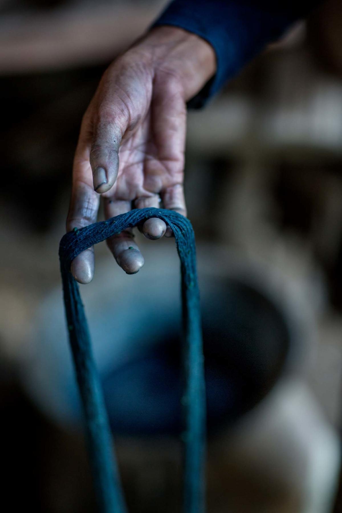 En indigofärgad garnhärva hålls upp av en hand.