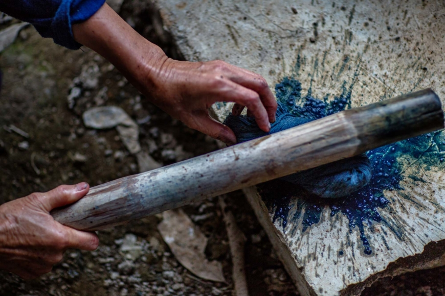 Vatten slås ur nyfärgat garn med hjälp av en pinne.
