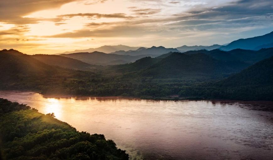 Landskap med i solnedgång med berg och vatten.