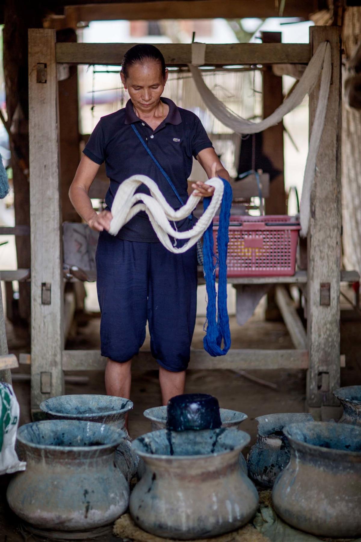 En kvinna står vid flera lerfat med indigo färg med en vit och en indigofärgad garnhärva i händerna.