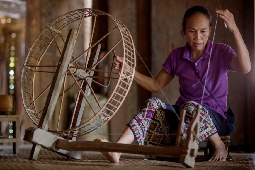 En kvinna spinner garn på en spinnrock.