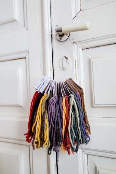 En ring med flera garnprover i olika färger hänger på ett dörrhandtag.