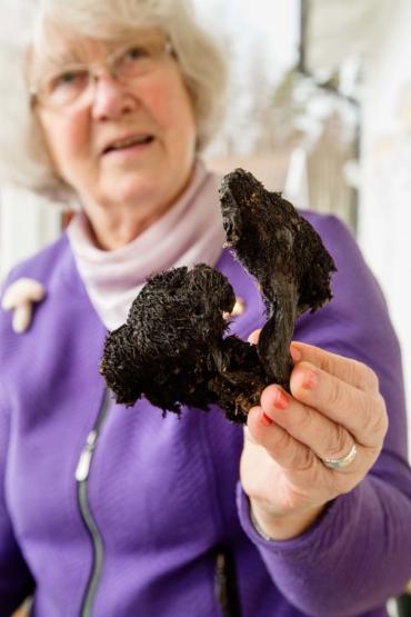 En kvinna håller upp två torkade svampar mot kameran.
