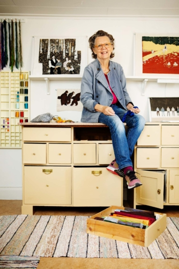 Elisabet Englund sitter och dinglar med benen på en byrå i sin ateljé