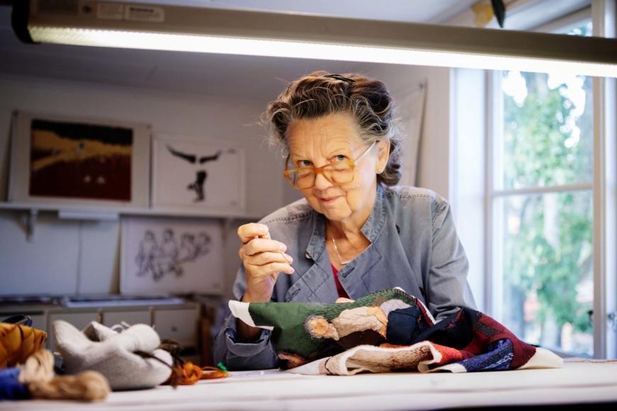 Elisabet Englund sitter och broderar under en stark lampa i sin ateljé