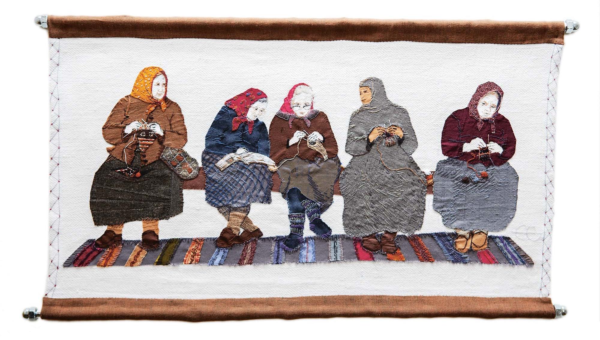 Broderi som föreställer fem kvinnor sitter och stickar tillsammans.
