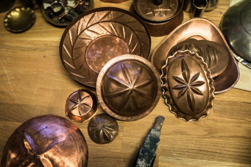 Flera kopparföremål i olika stadier av tillverkningsprocessen.