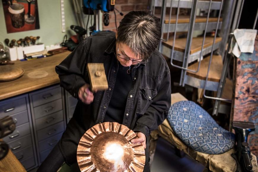 Michaela Ivarsdotter formar kopparplåt med hjälp av en hammare.
