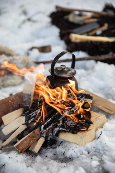Kaffepanna på öppen eld i en snöig skog.