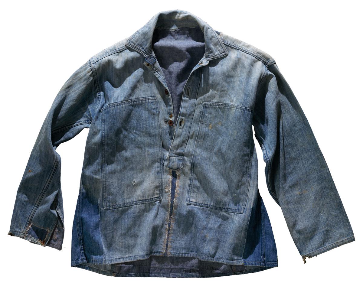 En sliten jacka i denim med flera lappar. Framsida.