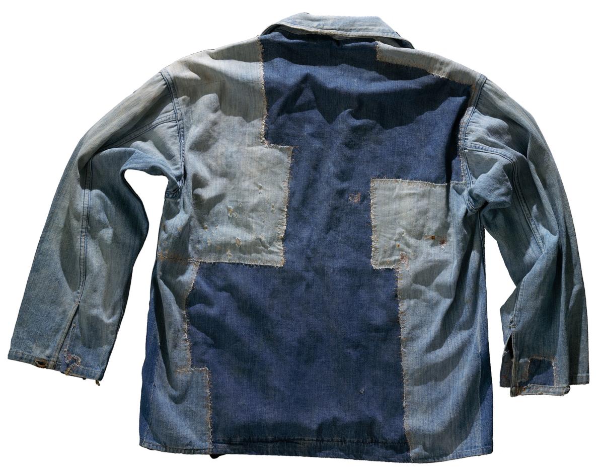 En sliten jacka i denim med flera lappar. Baksida.
