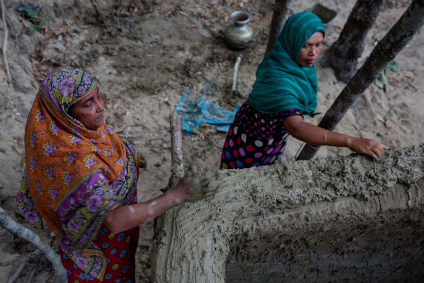 Ambia Kathu och Johora Begum bygger på en vägg.