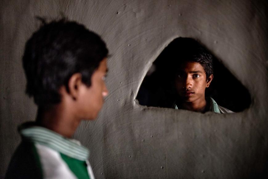 Mohammad Rabiul Alam står och tittar in i en trekantig spegel inmonterad i väggen.