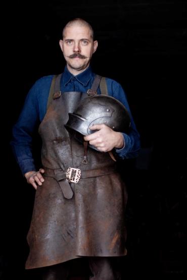 Albert Collins med skinnförkläde, håller i en smidd riddarhjälm.