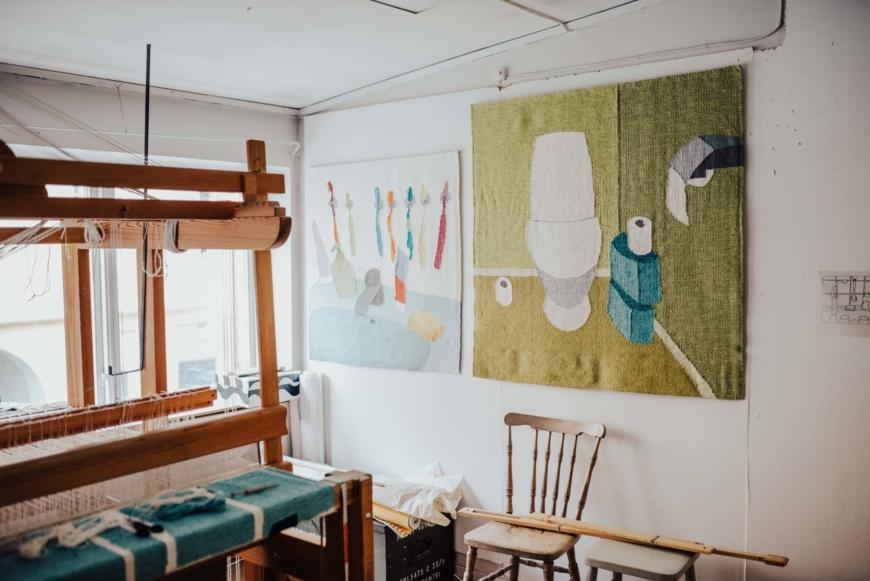 En vävstol står till vänster i bild, på väggen bakom hänger en väv med ett handfat där det finns tvål, tandkräm och flera tandborstar och en med en toalettstol med flera rullar toalettpapper.