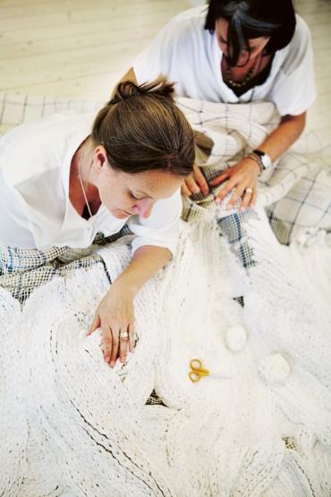 Katarina Evans och Katarina Brieditis med en vit flätad matta