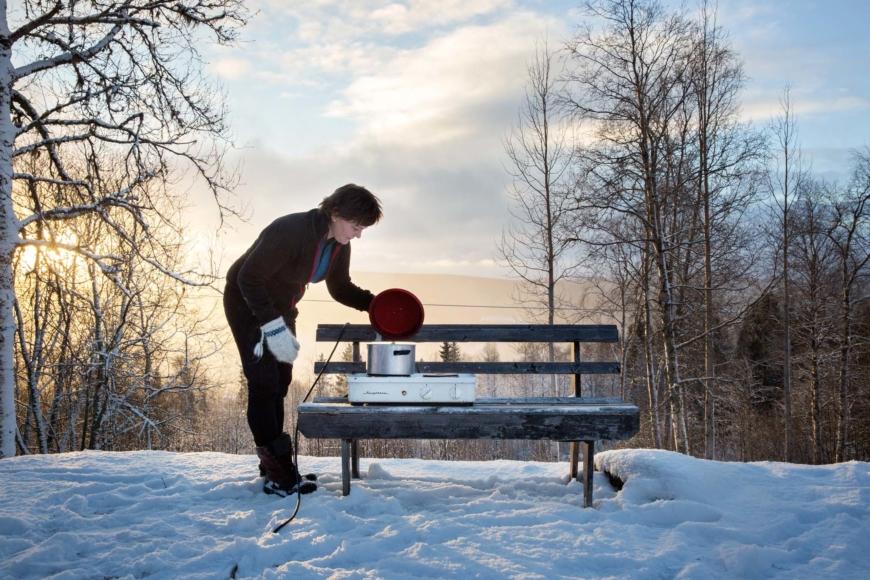 Helena Gjaerum står vid en träbänk utomhus och kokar något på en liten spis.