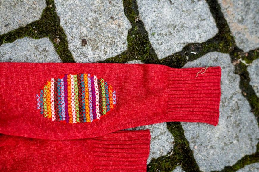 En röd stickad tröja med korstygn över en sliten armbåge.